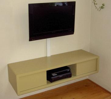 Zwevende TV kast van gelakt MDF met greeploze deurtjes.